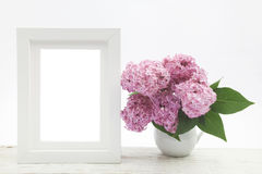 Bunch lilac in vase on wooden table and white frame mock up. Bunch lilac in vase on wooden table and white frame Royalty Free Stock Image