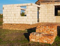 Bunch of lined up old bricks on the pallet on the sunset, unfinished house on the background. Pile of old red bricks on the pallet on the sunset, house under royalty free stock photos