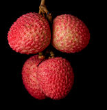 A bunch of lychees against a black background Stock Image