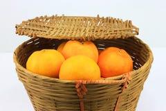 A bunch of mandarin orange in rattan basket Stock Photos