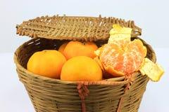 A bunch of mandarin orange in rattan basket Royalty Free Stock Image