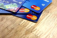 A bunch of Mastercard and Visa credit cards spread on a wooden table Royalty Free Stock Images