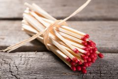 Bunch of matchsticks with red heads. Horizontal photo with Bunch of long wooden matchsticks with red heads which are bonded by piece of yellow dry straw. Bunch Stock Photos