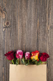 Bunch of multicolor rose flowers in paper envelope over wooden b Royalty Free Stock Photo