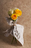 Bunch of multicolor rose flowers wrapped in newspaper over brown Royalty Free Stock Images