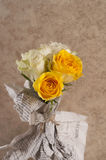 Bunch of multicolor rose flowers wrapped in newspaper over brown Stock Photos