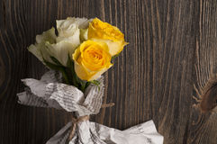 Bunch of multicolor rose flowers wrapped in newspaper over woode Stock Photography