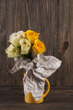 Bunch of multicolor rose flowers wrapped in newspaper over woode Stock Photo