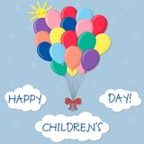 A bunch of multicolored balls with a red bow isolated on the sky background. Clouds and sun. Happy children`s day. Cartoon flat style. Vector stock illustration