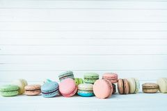 Bunch of multicolored macaroons or macaron on a white wooden background, almond cookies on a table, copy space. Bunch of multicolored macaroni or pasta on a Royalty Free Stock Images