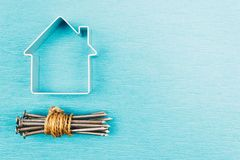 A bunch of nails and a house symbol on a blue table. Copy space for text stock images
