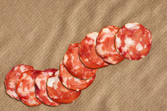 Bunch Of Nine Pork Salami Slices Set On Crumpled Striped Manila Brown Kraft Paper Stock Photos