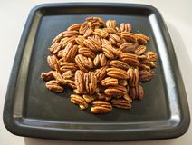 A bunch of nuts pecan on a black plate. Close-up photo stock illustration
