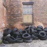 Bunch o' tires. Random tires next to an abandoned building stock photos