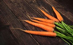 Free Bunch Of Fresh Carrot Roots With Green Leaves On Dark Old Wooden Board Royalty Free Stock Photography - 162994177