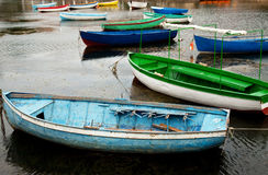 Bunch of old boats in calm water. Old boats in calm water. blue one at the front with broken seat Stock Image