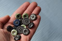 A bunch of old colored buttons on an open palm above the table. A bunch of old colored buttons on an open palm above a gray table Stock Photography