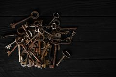 Bunch of old metal keys on a table, top view, low key. Theme of collecting, vintage decoration, safety concept. Bunch of old metal keys on a wooden table, top royalty free stock photos