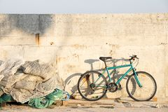 Bunch of old weathered trawl fishing nets and a parked bicycle on fishing village pier. On a sunny day royalty free stock photos