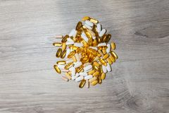 Bunch of Omega 3 tablets and capsules, carnitine, creatine, fat burners, BCAA or testosterone booster. Sports medical vitamins and. Preparations on a wooden royalty free stock photography