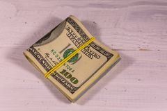 Bunch of the one hundred dollar bills with rubber on wooden tabl. Bunch of the one hundred dollar bills with rubber on white wooden table Royalty Free Stock Image
