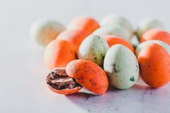 Bunch of orange and green little eggs. On white background. Easter candy Royalty Free Stock Photo