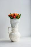 Bunch of orange tulips in the vase. Bright orange tulips in the white vase on white background Royalty Free Stock Photos