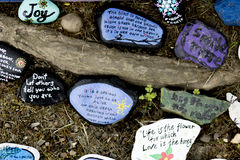 Bunch of painted rocks. Painted rock with quotes and art on them royalty free stock image
