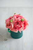 Bunch of pale pink ranunculus persian buttercup  light background, wooden surface. green box Stock Image