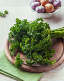 Bunch of  parsley on wooden chopping board Royalty Free Stock Images