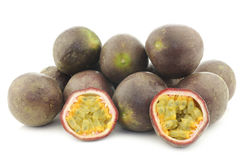 Bunch of passion fruits and a cut one Royalty Free Stock Photos