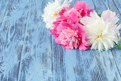 bunch of pastel pink peony with green leaves on the wooden floor stock photo