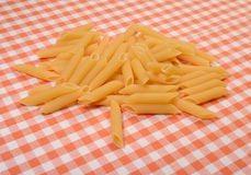 Penne pasta. Bunch of penne pasta on a red and white background Stock Photos