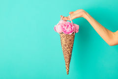 Bunch of peonies flowers in female hand on a turquoise wall background. Copy space Stock Image