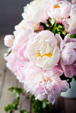 Bunch of peony flowers  in an enamel jar. Bunch of peony flowers with green leaves in an enamel jar on a wooden background Stock Photo