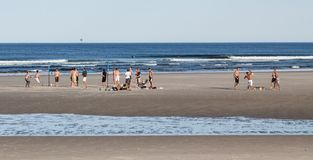 Playing Ball on the Beach in Summer. Bunch of people playing volleyball on the beach with surfer in the water during summer at Ogunquit Beach in Maine Stock Images