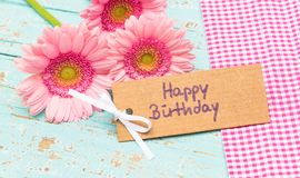 Happy Birthday greeting card with pink gerbera daisy flowers. Bunch of pink gerbera flowers with a greeting card for Happy Birthday on pastel blue wooden table stock photos