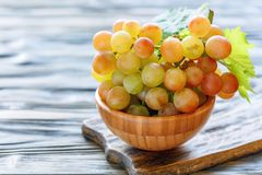 Bunch of pink grapes in a wooden bowl. Royalty Free Stock Photos