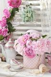 Bunch of peony in shabby chic style interior Stock Photography