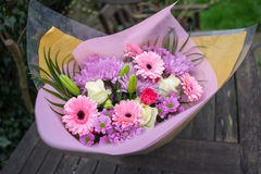 Bunch of pink red and white flowers. With green leaves wrapped up in pink paper Royalty Free Stock Images