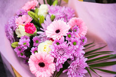 Bunch of pink red and white flowers. With green leaves wrapped up in pink paper Stock Photography
