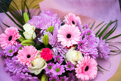 Bunch of pink red and white flowers. With green leaves wrapped up in pink paper Royalty Free Stock Photography