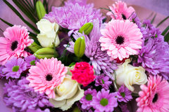Bunch of pink red and white flowers. With green leaves wrapped up in pink paper Royalty Free Stock Photo