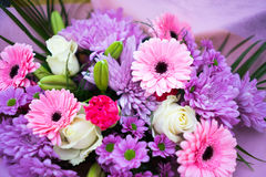 Bunch of pink red and white flowers. With green leaves wrapped up in pink paper Royalty Free Stock Photos