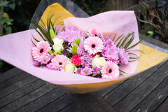 Bunch of pink red and white flowers. With green leaves wrapped up in pink paper Stock Images