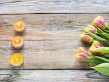 Bunch of pink tulips with candles on rustic wooden background Royalty Free Stock Photography