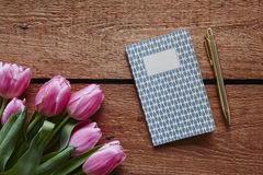 A bunch of pink tulips writing in a notebook spring atmosphere. Notes for easter shopping writing a poem valentines surprise Stock Image