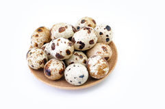 Bunch of quail eggs on a brown plate isolated on white Royalty Free Stock Photography