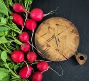 Bunch of radish with empty board. On the black stone background Stock Image