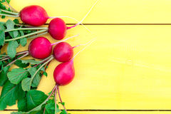A bunch of radishes on a wooden table. Five radishes with tops lie on a wooden table. The objects in the photo are located on the left Royalty Free Stock Photo